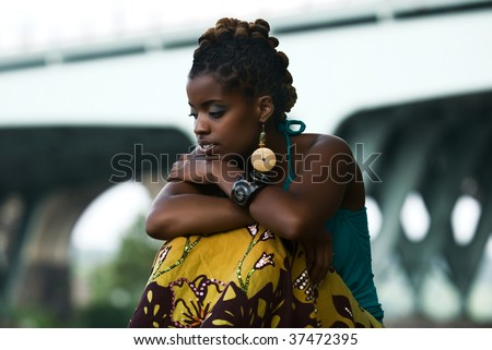 African American woman sits and thinks - stock photo