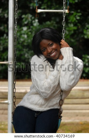 African-American woman sitting in a swing on a fall day - stock photo