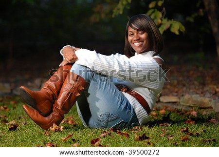 African -American woman sitting on grass smiling - stock photo
