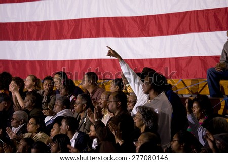 African American woman standing in front of American Flag at Barack Obama Presidential Rally, October 29, 2008 in Rocky Mount High School, North Carolina - stock photo
