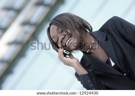 African american woman talking on the hand phone outside an office environment. - stock photo