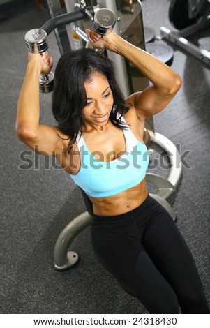 african american woman training or exercising in gym, weight lifting for tricep - stock photo