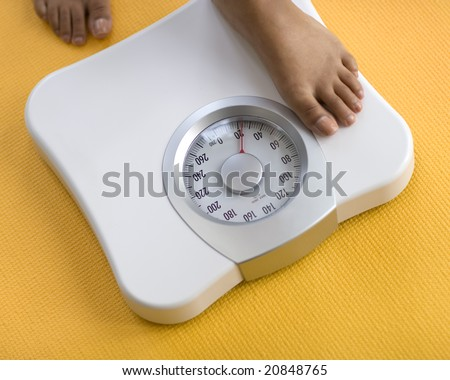 African American Woman weighing herself on a bathroom scale - stock photo