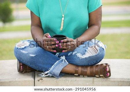 African American woman with beautiful manicure and pedicure sits on the bench and holds a cap with drink - stock photo