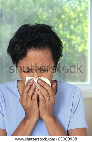 African American woman with cold or allergies sneezing into tissue - stock photo