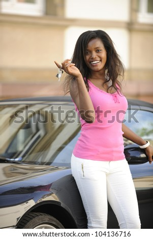 african american  woman with her new car showing key - stock photo