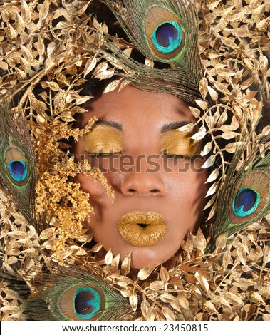 African American Woman Wrapped in Metallic Leaves and Peacock Feathers - stock photo