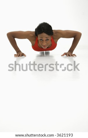 African American young adult woman doing push up and looking at viewer.