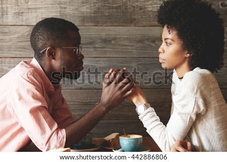 African American young couple sitting at a cafe table: black man in glasses holding her beautiful wife's hands, begging her to forgive him, apologizing for an affair, looking with guilty expression - stock photo