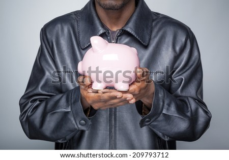African american young man holding a piggy bank  - stock photo