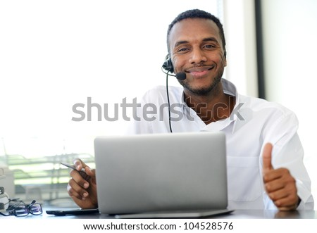 African American young operator with headset and laptop at workplace showing thumb up - stock photo