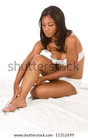 African-American young woman in white lingerie sitting on bed sheet and massaging her legs. - stock photo