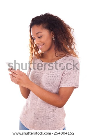 African American young woman sending a text message on her smartphone - Black teenager people - stock photo