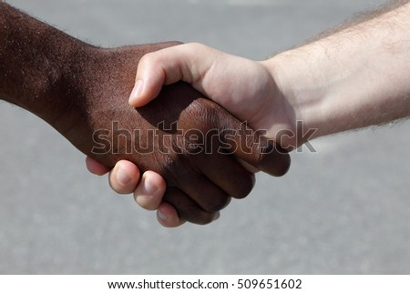 African and Caucasian men shaking hands outdoors.