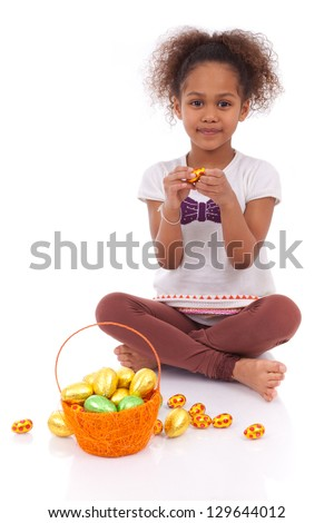 African Asian girl holding chocolate ester egg, isolated on white background - stock photo