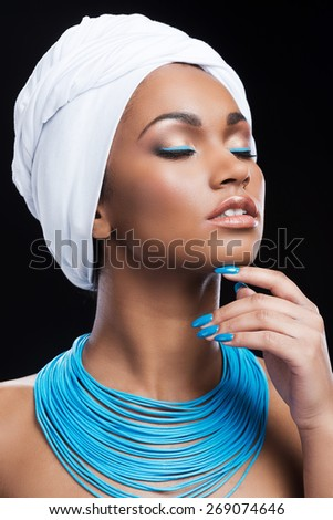 African beauty in style. Beautiful African woman wearing a headscarf and touching her chin while keeping eyes closed and standing against black background - stock photo
