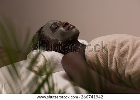 African beauty woman getting mud mask at spa - stock photo