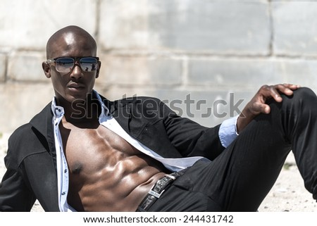 African black man model with six pack in black suit and unbuttoned white shirt, wearing sun glasses on beach with concrete wall background - stock photo