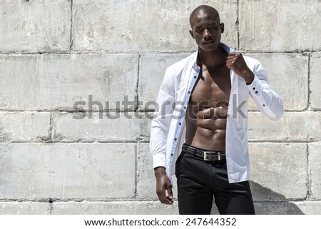 male model with shirt open leaning against brick wall