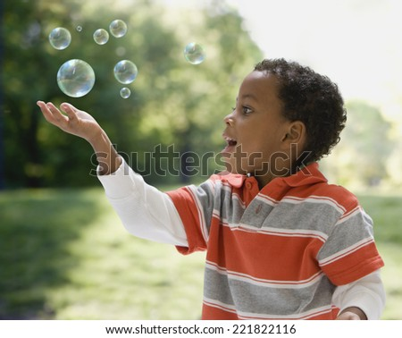 African boy catching bubbles - stock photo