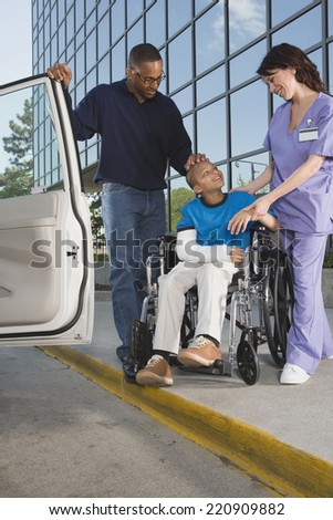 African boy in wheelchair leaving hospital with father - stock photo