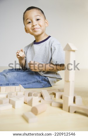 African boy playing with wooden blocks - stock photo