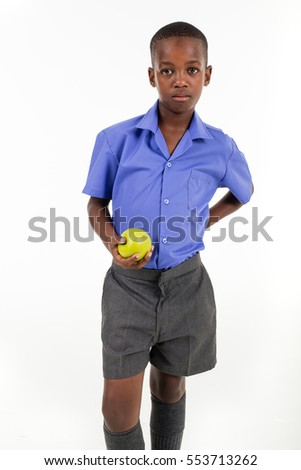 African boy wearing his school uniform holding an green apple ready to go back to school.
