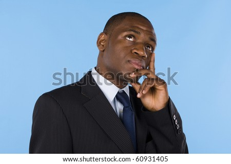 African business man with a pensive expression looking up - stock photo