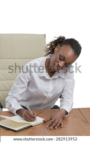 African business woman sitting at her desk and planning isolated on white background - stock photo