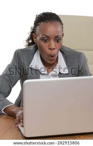 African business woman sitting at her desk and working with laptop isolated on white background - stock photo