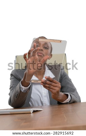 African business woman sitting at her desk and working with tablet computer isolated on white background - stock photo