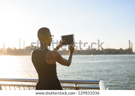 African business woman working on the tablet outdoor, close up, New York, Manhattan, skyline view