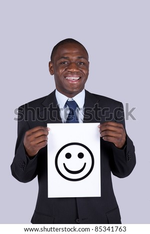 african businessman holding a happy face symbol printed on a paper - stock photo