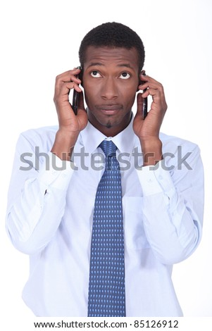 African businessman holding two telephones - stock photo