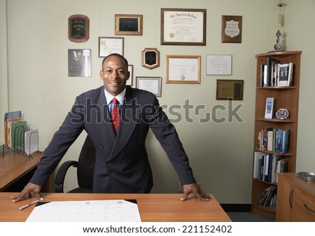 African businessman leaning on desk - stock photo