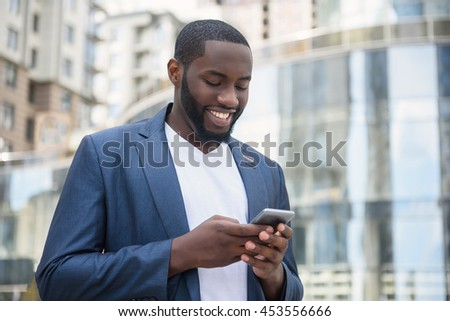 African businessman messaging in big city - stock photo