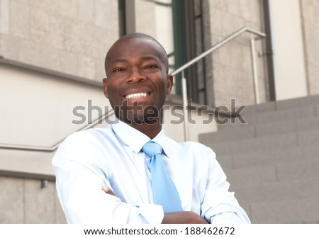 African businessman on stairs laughing at camera - stock photo