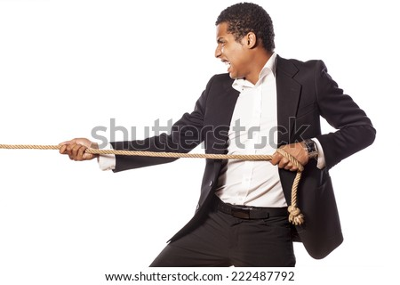 African businessman pulling a rope on white background - stock photo