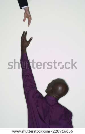 African businessman reaching up for hand - stock photo