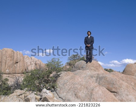 African businessman standing on top of rock - stock photo