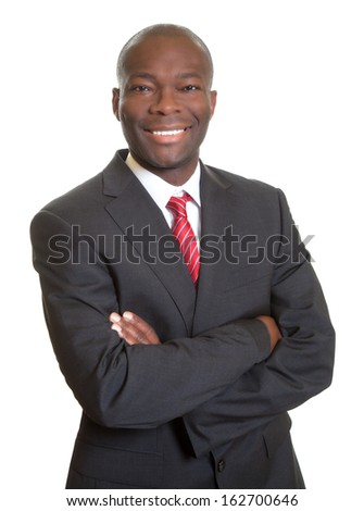 African businessman with crossed arms laughing at camera - stock photo