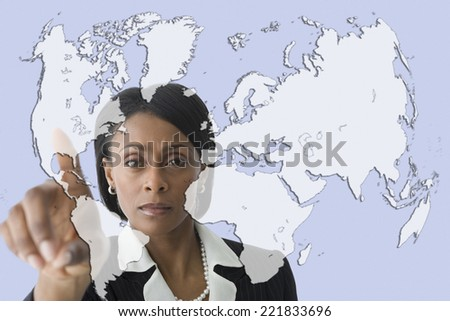 African businesswoman pointing to world map - stock photo