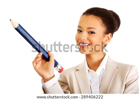 African businesswoman pointing up with big pencil. - stock photo