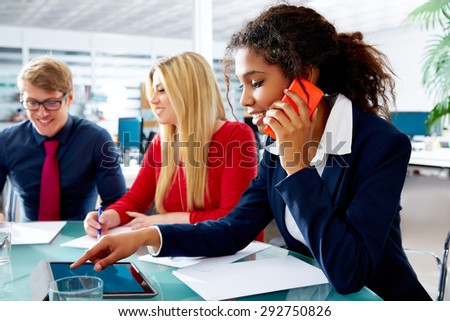 African businesswoman talking phone and touch pad in teamwork meeting at office - stock photo