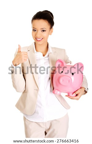 African businesswoman with piggybank and thumbs up.