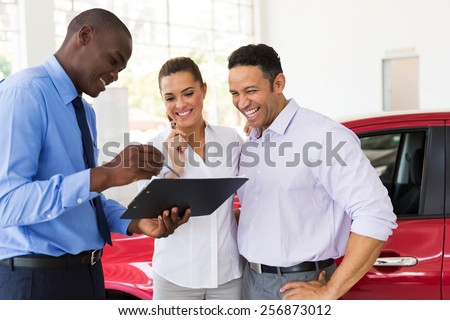 african car dealer explaining sales contract to couple buying a car - stock photo