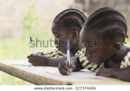 African Children at School Doing Homework. African ethnicity students writing their essay in an African school. They're holding blue pens to write down their homework whilst sitting in their desk. - stock photo