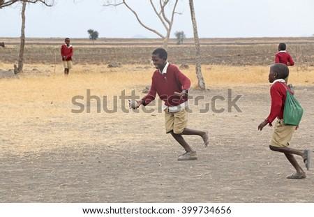 African Children at School / Schoolboys playing with a sock ball in a primary school near Karatu, Tanzania / Photo taken at Nanja Primary School, Karatu, Tanzania on October 7, 2015  - stock photo