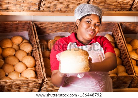 african colored sales lady holding out fresh baked bread loaf standing in front of baskets of bread buns - stock photo