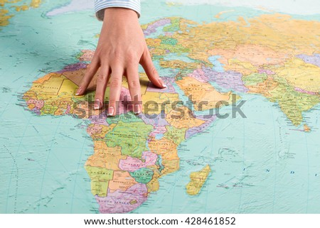 African continent on world map. Female hand shows African continent. Briefing at intelligence agency. Search and recruit. - stock photo